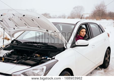 Young woman waiting for help or assistance after her car breakdown in the winter. Broken down car with open hood on a country road.