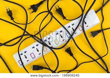 Messy of electrical cords and wires unconnected electrical power strip or extension block with messy wires top view on colorful background messy electric equipment flat lay concept.