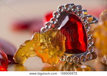 Pieces of cannabis oil concentrate aka shatter in abstract background with red hearts - marijuana valentine concept