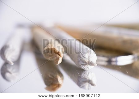Close up of assorted rolled marijuana joints on reflective white background