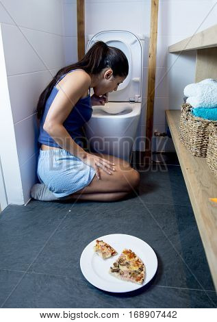 young sad and depressed bulimic woman feeling sick guilty vomiting and throwing up kneeling on floor of toilet WC guilty after eating pizza in nutrition disorder bulimia and anorexia concept
