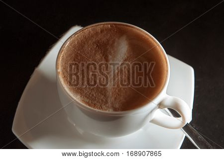Cappuccino cup overhead view on dark background vintage color-look