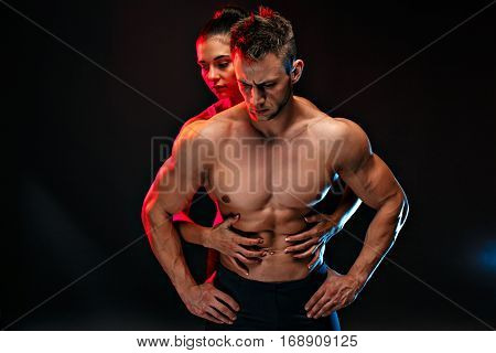 Two fit sportspeople posing together, close to each other. Studio portrait.