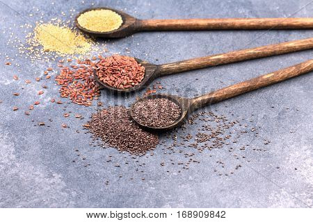 collection of healthy grains in wooden spoon on stone textured background. Chia seeds, grain amaranth and flaxseeds.