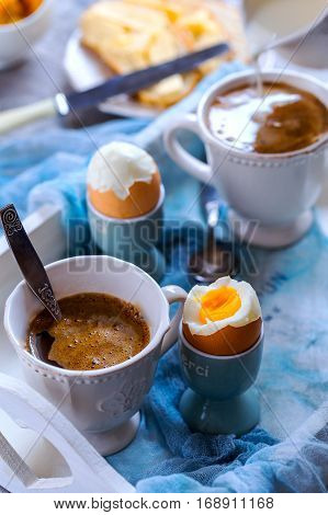 Breakfast for two. Strong coffee and 2 eggs hard boiled. Eggs and coffee are located on the white wooden tray.