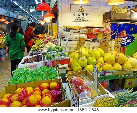 North Point, Hong Kong - February 13, 2016: Booth with fresh fruits and vegetables on the Java Road Market in North Point, Hong Kong. Customers are at the booth and buy food.