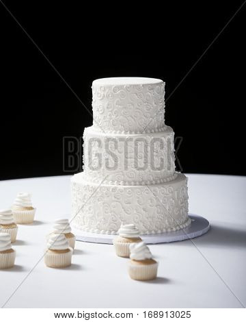 Three tiered wedding cake and cupcakes on table with black background