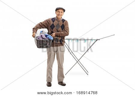 Full length portrait of a senior holding a laundry basket full of clothes in front of a clothing rack dryer isolated on white background