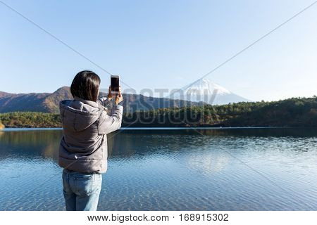 Woman taking picture on Mount Fuji by mobile phone