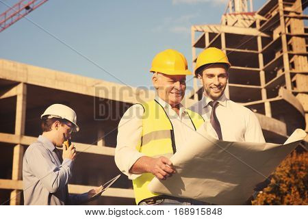 Engineer with drawing and worker standing against unfinished building
