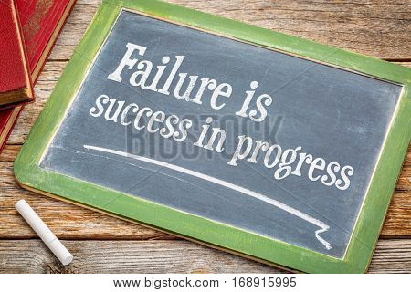 Failure is success in progress - inspirational text on a  slate blackboard with a white chalk and a stack of books against rustic wooden table