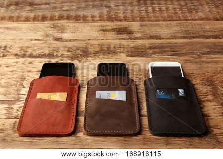 Leather cases with mobile phones and credit cards on wooden background