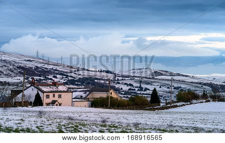 Houses and peaks covered by snow in Greater Manchester England.