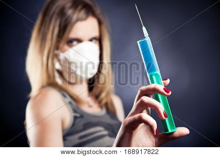 young woman with flu mask, holding a syringe. selective focus on the syringe, face is out of focus.