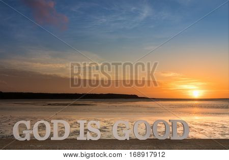 3D words saying 'lGod is good' as the sun goes down into clouds over a river lagoon.