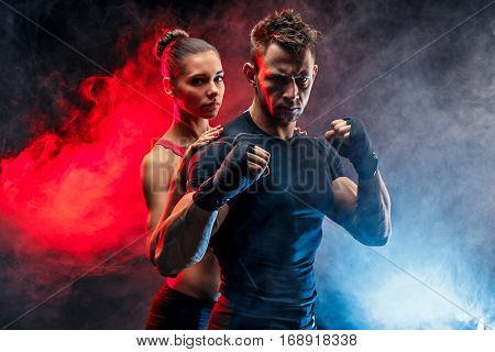 Strong boxer in stance with handwraps on his fists. With girlfriend standing behind him.