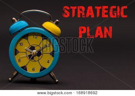 Strategic Plan Written With Alarm Clock On Black Paper Background