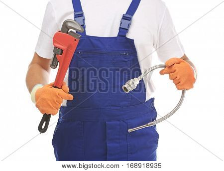 Young handsome plumber with pipe wrench and flexible hose on white background