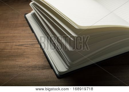 White pages of notepad on the wooden table.