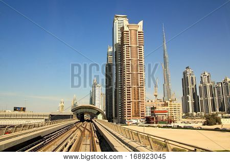 DUBAI UAE - JANUARY 27: Dubai automated metro railways view with skyscrapers of Downtown Dubai and Burj Khalifa on January 27 2017 Dubai UAE.