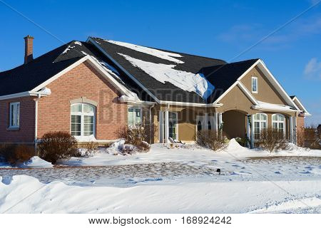 North American brick detached home after a snowfall.