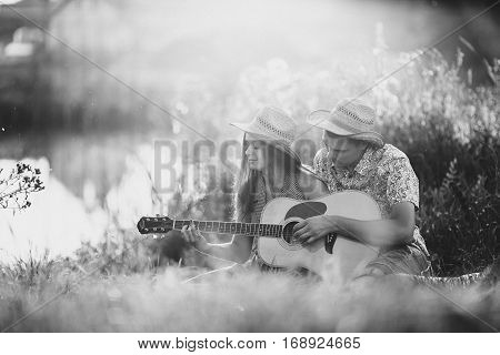 White and black portrait of couple of brunette girlfriend and boyfriend sitting on grass at meadow smiling and having fun together. Man singing and playing on guitar. Woman sensuality looking down.