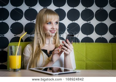 Young student girl texting sms using a smartphone and drinking orange juice at the cafe