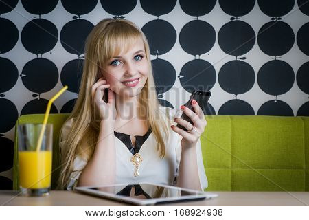 Young girl texting sms using a mobile phone and drinking orange juice at the cafe