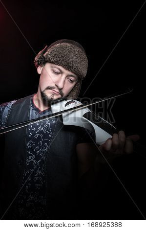Funny bearded man in a winter hat plays on a white electric violin, isolated on a black background