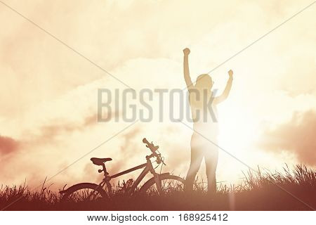 Silhouette of happy sporty woman standing with raised arms near her bike and celebrating achievement against glowing sunshine on sunrise or sunset - success or healthy lifestyle concept