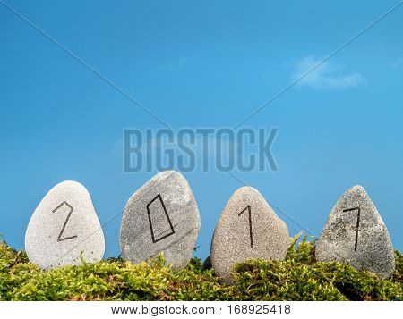 New Year 2017 date engraved in four stones in Runic alphabet style over blue sky