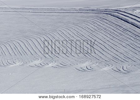 Tracks of a snowplow offside the slopes of the ski region of the Hintertuxer Glacier (Tuxer Ferner) in Tyrol Austria