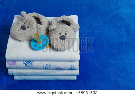 Set of the diapers with booties and nipple on the blue background with copy space