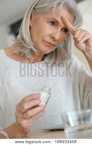 Senior woman taking pill to ease migraine