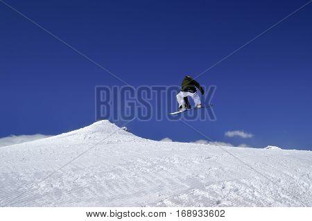 Snowboarder Jump In Terrain Park At Ski Resort On Sun Winter Day