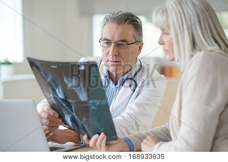 Doctor with patient looking at X-ray in office
