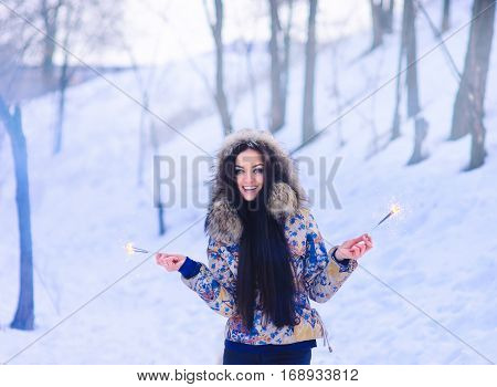 Cheerful Girl Holding Sparklers In Winter Forest