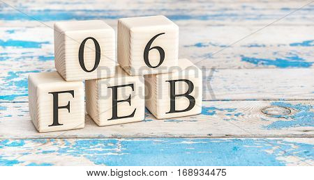 February 6th. Wooden cubes with date of 6 February on old blue wooden background.
