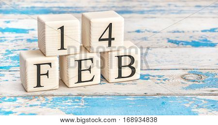 February 14th. Wooden cubes with date of 14 February on old blue wooden background.