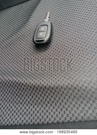 Key car and remote control over car seat. Photo