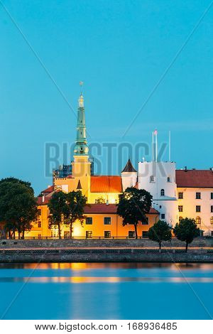 Latvia. Riga Castle, Famous Historical Cultural Medieval Landmark Of Late Classicism And Official President Residence On Embankment Of Daugava River In Evening Illumination With Summer Blue Sky.
