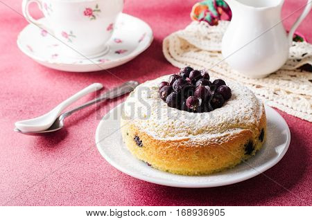 Blackcurrant cake on pink background with tea, horizontal