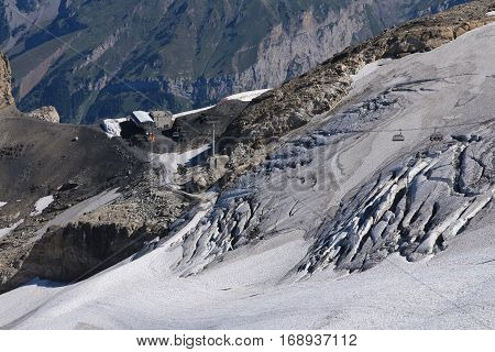 Rugged glacier on top of mount Titlis and chair lift.
