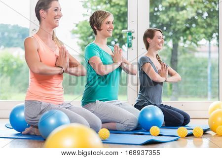 Young women doing  yoga during postnatal recovery lesson