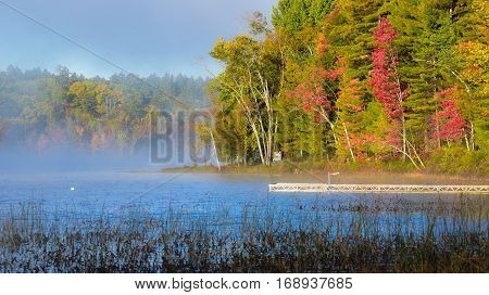 Late-summer, morning sun shines on mist rising from warmer wooland lake water.  Dock extends from lakeside cottage country in a deciduous waterfront forest.
