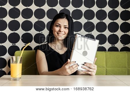 Brunette model aged 20s sitting at the table poses for camera indoors