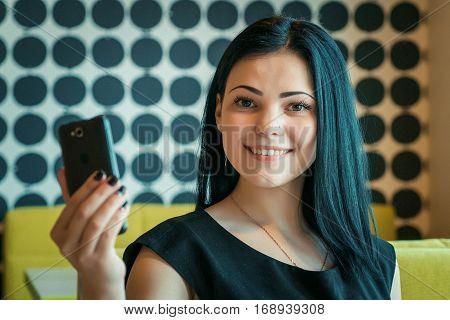 Brunette girl making selfie photo using a mobile phone during coffee break