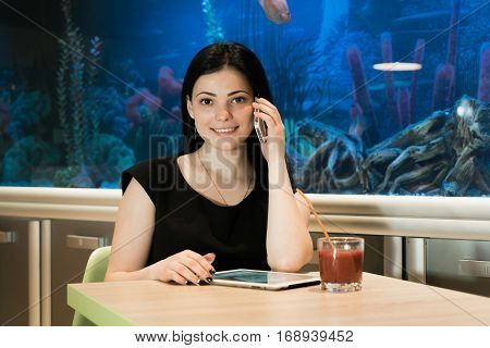 Stylish brunette woman sitting at a cafe drinking juice and talking on a cellphone in the background blue aquarium