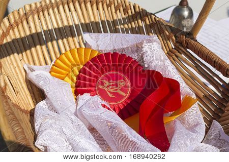 Award rosettes for winner in equestrian sport and horse show red and yellow colors with ribbons in basket