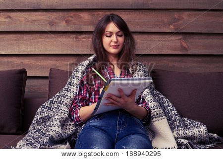 Mid shot of student studying while sitting on the sofa. Covered under blanket. Wearing casual clothes, trying to concentrate